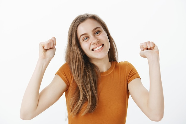 Primo piano della ragazza giovane carina allegra che si rallegra, alzando le mani in segno di evviva, pompa del pugno e sorridente, trionfante sulla vittoria