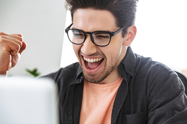 Крупным планом веселый красавец в очках с помощью портативного компьютера и радуется, сидя за столом в офисе