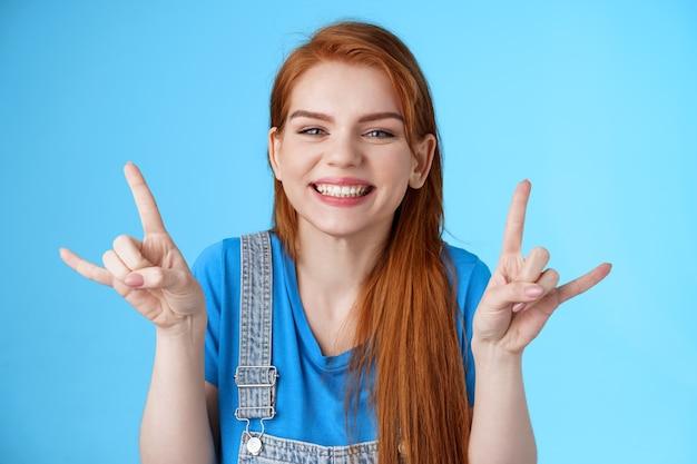 クローズアップ陽気な幸運な楽しい赤毛の女性を楽しんで、夏を楽しんで、ロックンロールのジェスチャーを見せて素晴らしいパーティーコンサートに出席し、ヘビーメタルの看板を作り、青い背景を笑顔