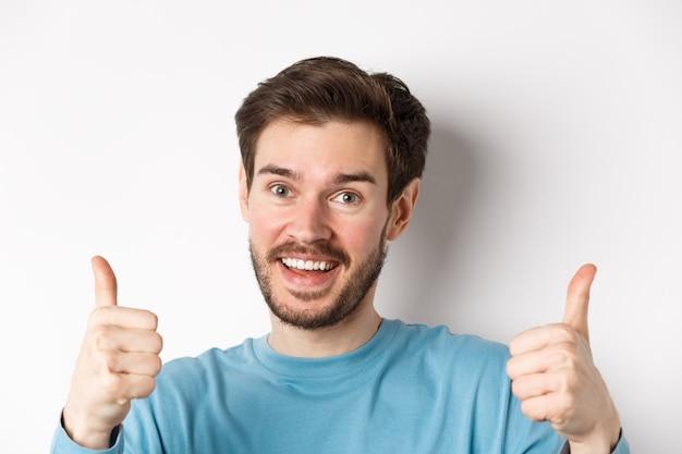 Il primo piano dell'uomo allegro dice di sì, mostrando i pollici in su in segno di approvazione, lodando il buon lavoro, sorridendo con approvazione, in piedi su sfondo bianco.