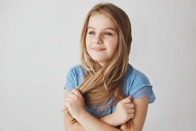 Close up of cheerful small blonde-haired girl with blue eyes holding hair with hands, looking aside with happy and relaxed expression.