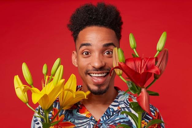Primo piano allegro giovane ragazzo afroamericano, indossa in camicia hawaiana, guarda la telecamera con espressione felice, si erge su sfondo rosso, viso coperto di fiori gialli.