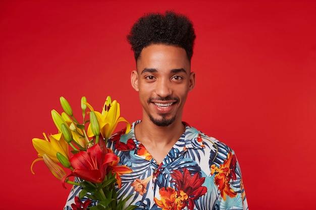陽気な若いアフリカ系アメリカ人の男をクローズアップ、アロハシャツを着て、幸せな表情でカメラを見て、黄色と赤の花を保持し、赤い背景の上に立っています。