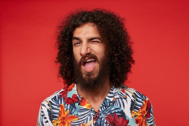 Primo piano di allegro giovane uomo riccio brunetta con la barba ammiccante e tenendo la bocca spalancata, vestito con una maglietta con stampa floreale