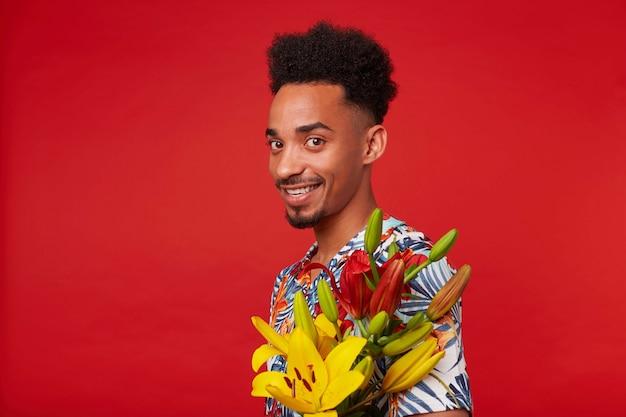 陽気な若い暗い肌の男をクローズアップ、アロハシャツを着て、幸せな表情でカメラを見て、黄色と赤の花を保持し、赤い背景の上に立っています。
