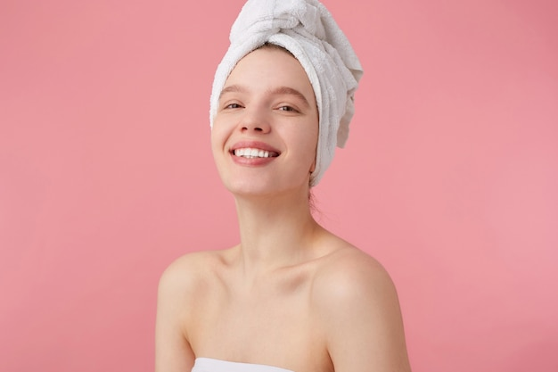 Close up of cheerful young lady after spa with a towel on her head, broadly smiles, looks happy and enjoyed, stands.