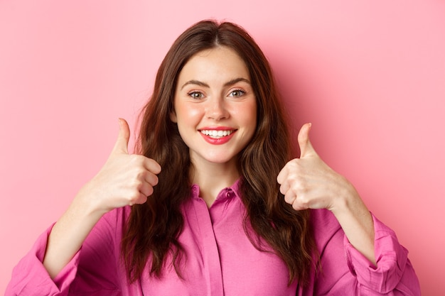 Close up of cheerful young lady fully approve your choice, praising something good, showing thumbs up and smiling pleased, pink wall.