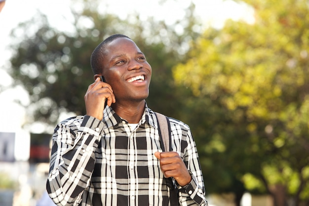Close up cheerful young man talking on cell phone outside