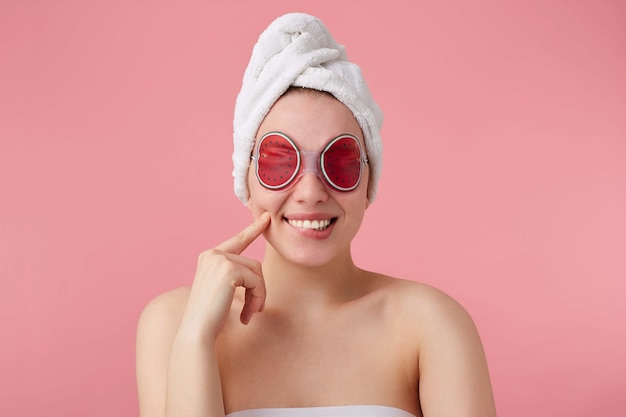 Close up of cheerful young woman after spa with a towel on her head, with mask for eyes, broadly smiles, feels so happy, touches cheek, stands.