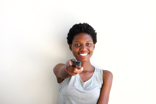 Close up cheerful young woman holding remote control and watching television at home