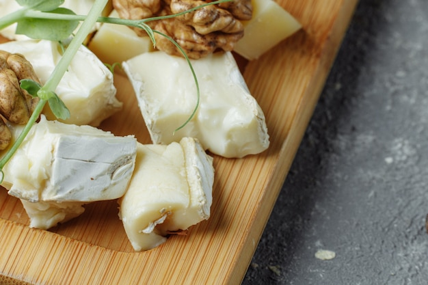 Close-up of a cheese plate. 4 types of cheese, soft white brie cheese, camembert, semi-soft briques, blue, roquefort, hard cheese