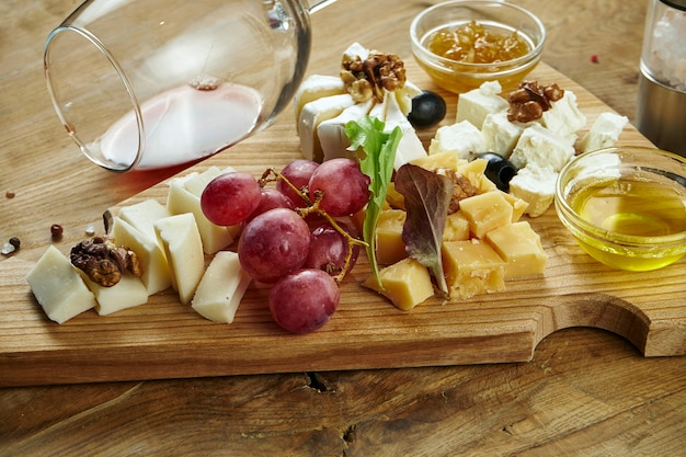 Close up on cheese plate served with nuts, grapes, honey. view from above on different types of cheese on dark surface
