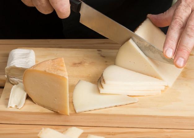 Formaggio del primo piano che affetta formaggio