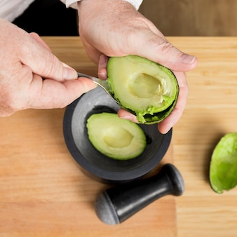 Close-up chef cleaning avocado