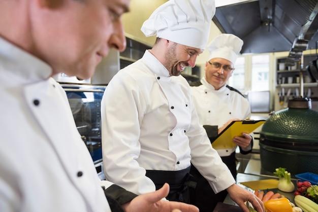 Chiuda in su chef che cucina nella cucina del ristorante