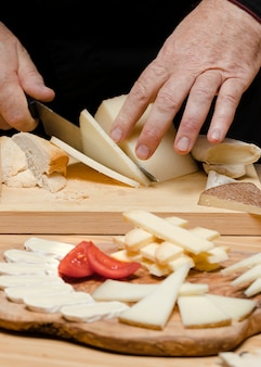 Close up chef cutting cheese on wooden board