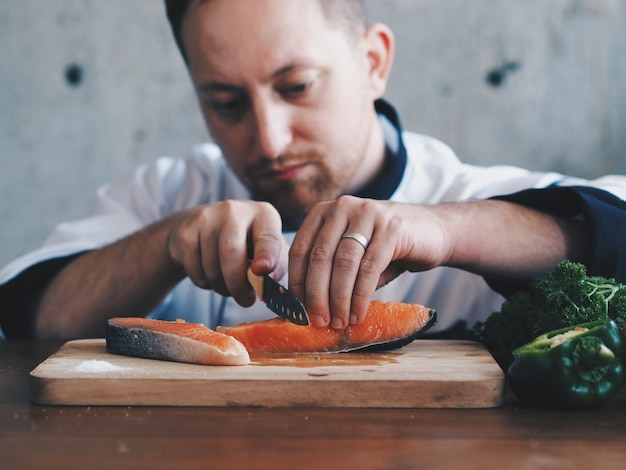 Close up chef cutting salmon on chopping board.