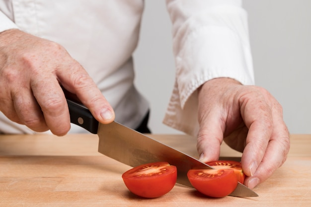 Close-up chef cutting tomatoes