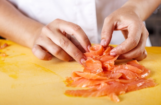 Close up of chef hands to serve salmon on flower shape in professional kitchen