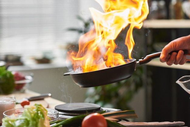 Close-up of chef holding pan he frying meat on open fire