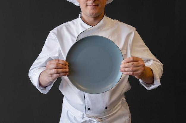 Крупным планом повар держит тарелку