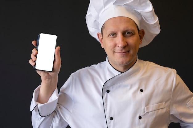 Крупным планом повар держит смартфон