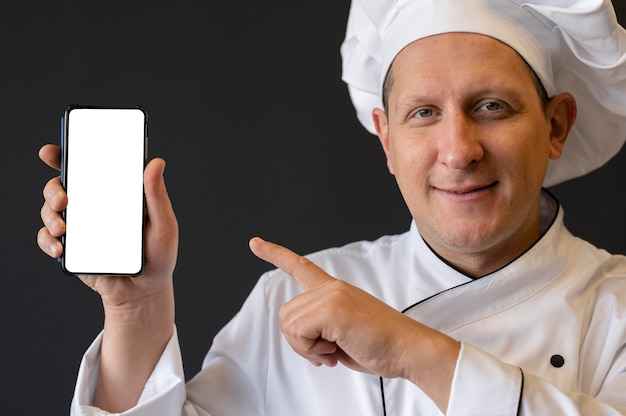 Close-up chef pointing at smartphone
