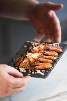 Крупным планом шеф-повар готовит пищу на тарелке