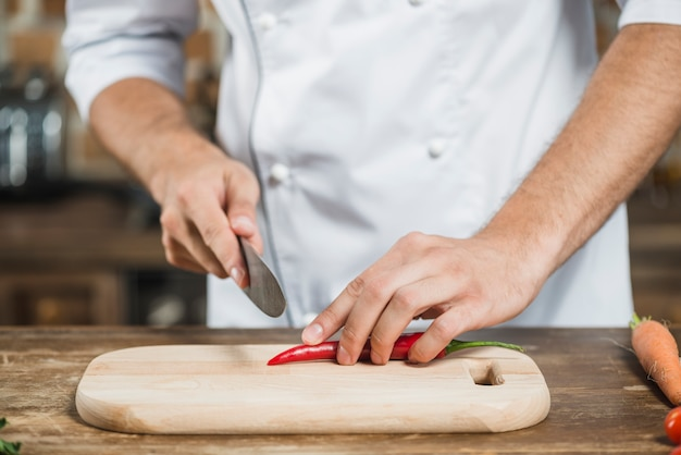 Close-up of chef's hand cutting red chili on chopping board