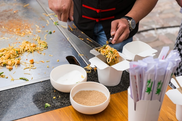 Close up of chef serving single portion of stir fried noodles in chinese take out box
