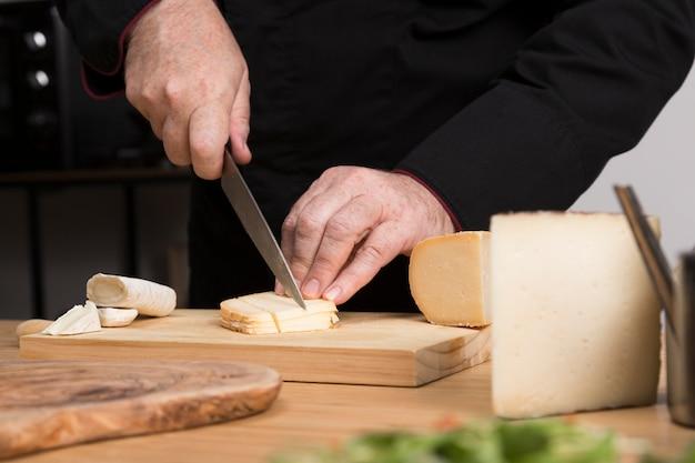 Cuoco unico del primo piano che affetta formaggio