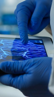 Close up of chemist doctor working on tablet with dna scan image analysing treatment results. scientist examining virus evolution using high tech researching vaccine development against covid19