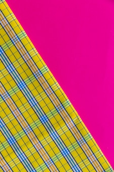 Close-up of chequered pattern textile on pink background
