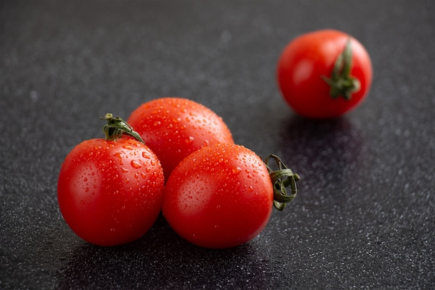 Close-up of cherry tomatoes with water drops with black background