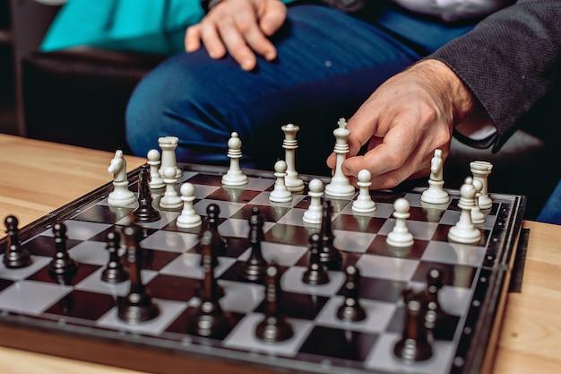 テーブルの上に立っているチェス盤を閉じます。白と黒の数字。男性の手の動く人物。