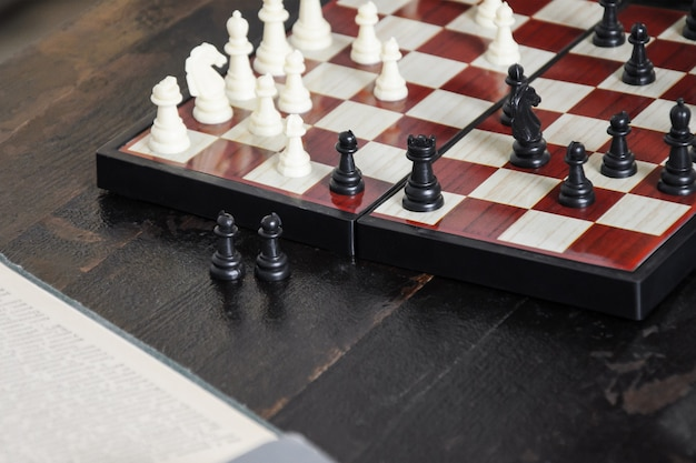 Close-up of chess pieces placed on chessboard at beginning of the game and stack of old books