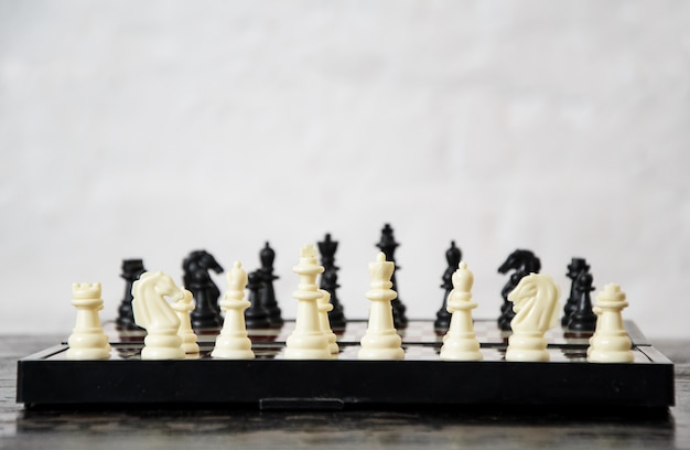 Close-up of chess pieces placed on chessboard at beginning of the game