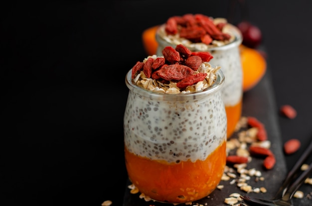 Close up of chia seed pudding with goji berries, smashed fresh apricot and oat meals on aslate board on black