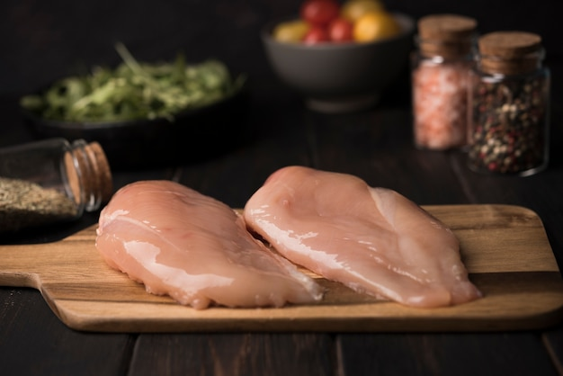 Close-up chicken breast on wooden board with ingredients