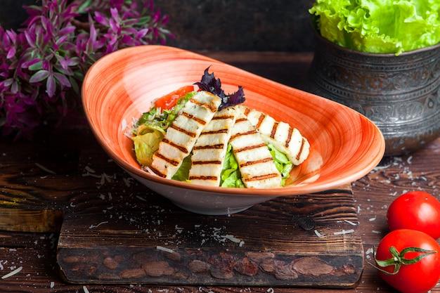 Chiuda sui petti di pollo arrostiti dell'insalata di caesar del pollo e sull'insalata fresca in piatto su una tavola di legno scura