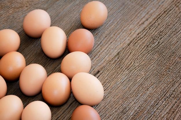 木製の背景にクローズアップの鶏の卵。茶色の卵、調理用