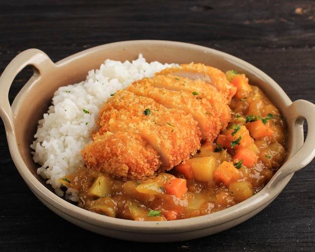 일본 카레로 치킨 카츠를 닫고, 나무 테이블 위의 갈색 세라믹 접시에 흰 쌀과 함께 제공, 텍스트 또는 레시피 복사 공간이 있는 검은색 테이블에 격리