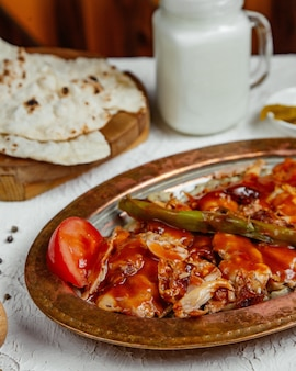 Close up of chicken kebab topped with tomato sauce