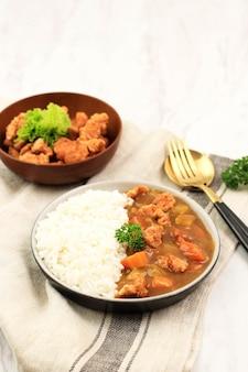 일본 카레를 곁들인 치킨 팝콘 카츠를 닫고 세라믹 접시에 흰 쌀과 함께 제공