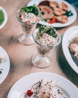閉じる。お祝いのテーブルでグラスを提供する新鮮な野菜とチキンサラダ