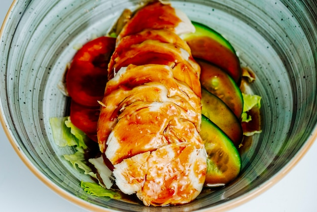 Close up of chicken side dish with cucumber, lettuce, bell pepper and soy sauce