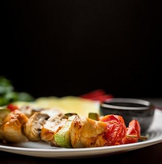 Close-up spiedini di pollo sulla piastra con salsa e patatine