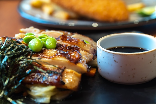 Close up of chicken steaks with cup of sauce on the black plate. green peas and japanese s