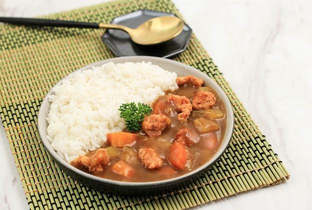 일본 카레를 곁들인 치킨 크리스피를 닫고, 흰색 테이블 위의 검은 세라믹 접시에 흰 쌀과 함께 제공