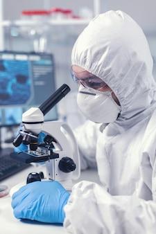 Primo piano dello scienziato capo ricercatore regola il microscopio in tempo dell'esperimento del coronavirus